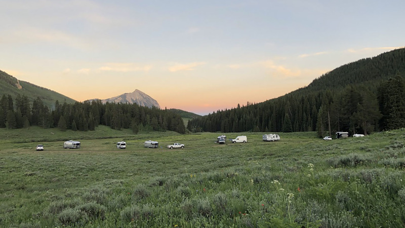 Multiple RV's camping for free in a field in Crested Butte, CO