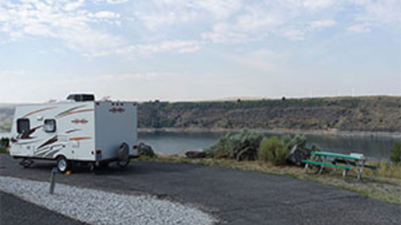 Travel trailer camping by water in a pull-thru campsite