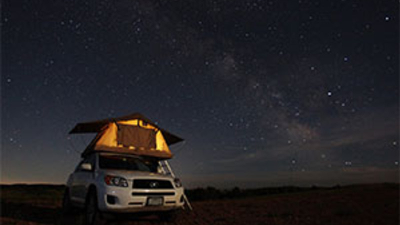 Car with a roof-top tent camping in North Dakota at night.