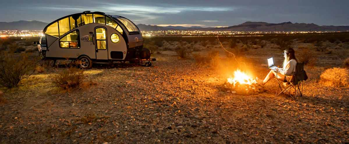 Teardop trailer in the desert with person sitting by blazing campfire with laptop in foreground, and city lights spanning the horizon in background