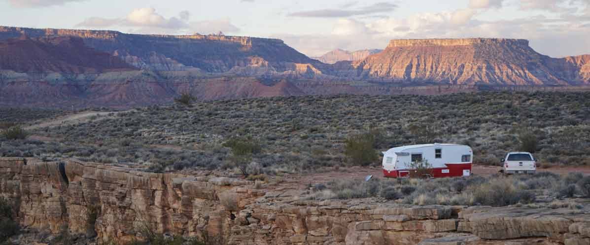 Older RV camped near rocky edge on sagegrass plain with buttes, bluffs, and rugged landscape in the background