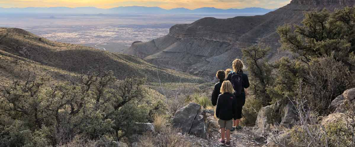 Parent and children on a hillside trail overlooking valley below, with ridgeline visible into the distance